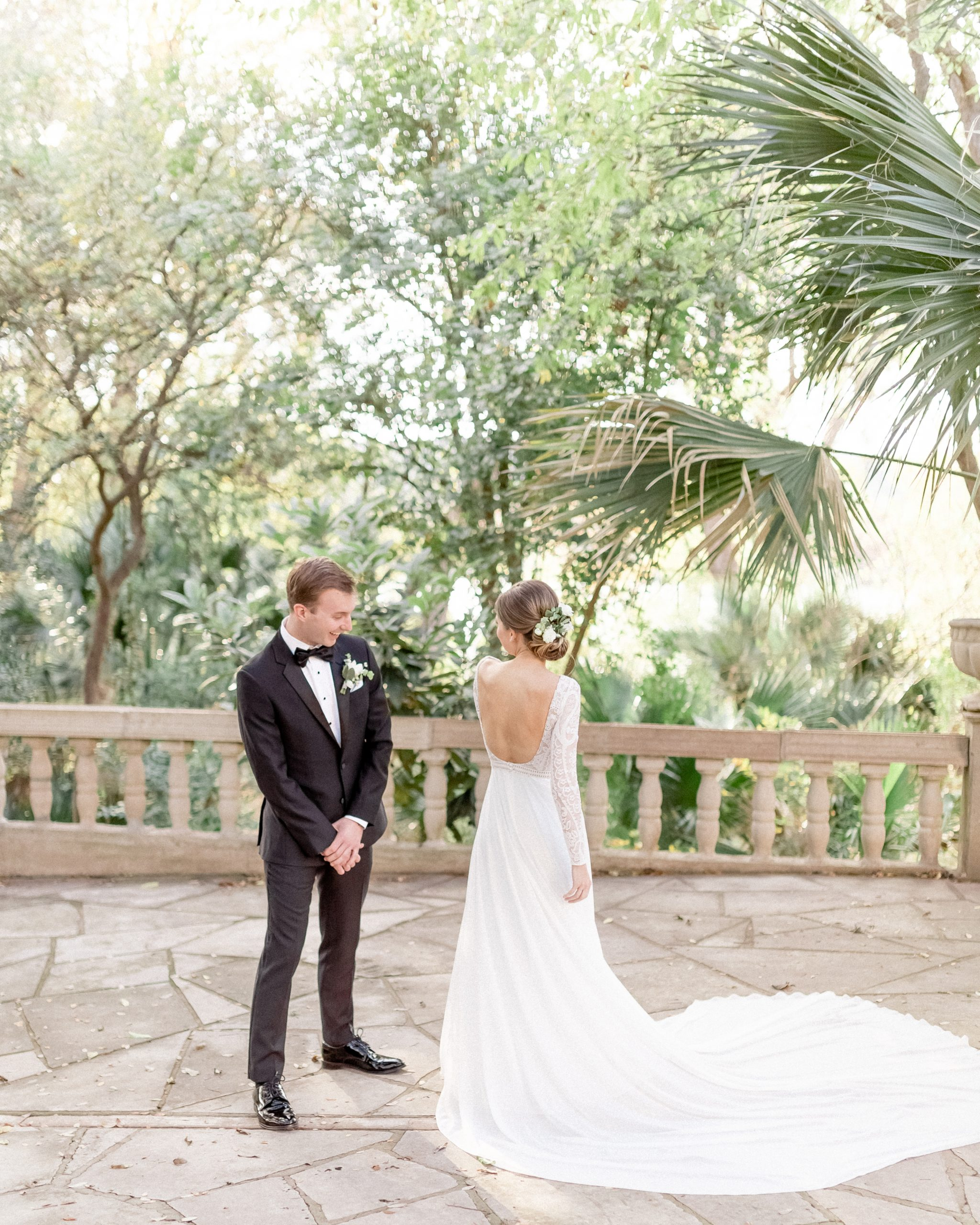 couple doing a first look in a green courtyard