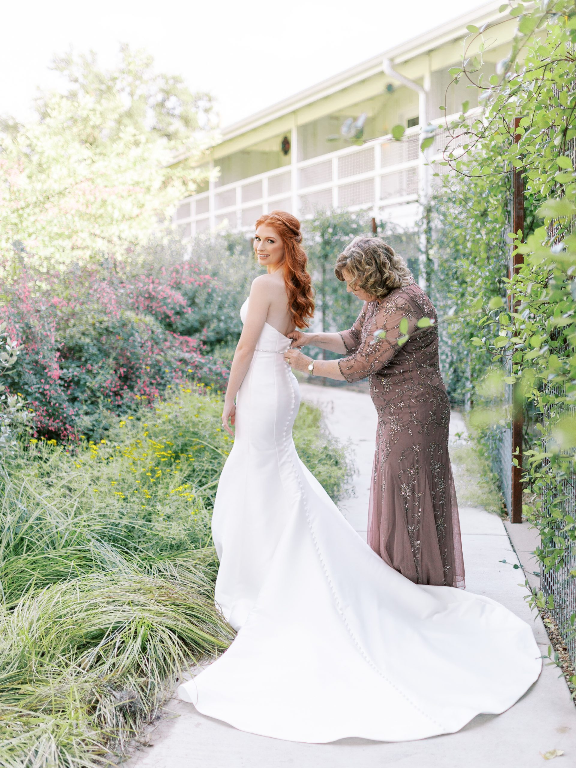 mom and bride putting on the bride's dress in garden