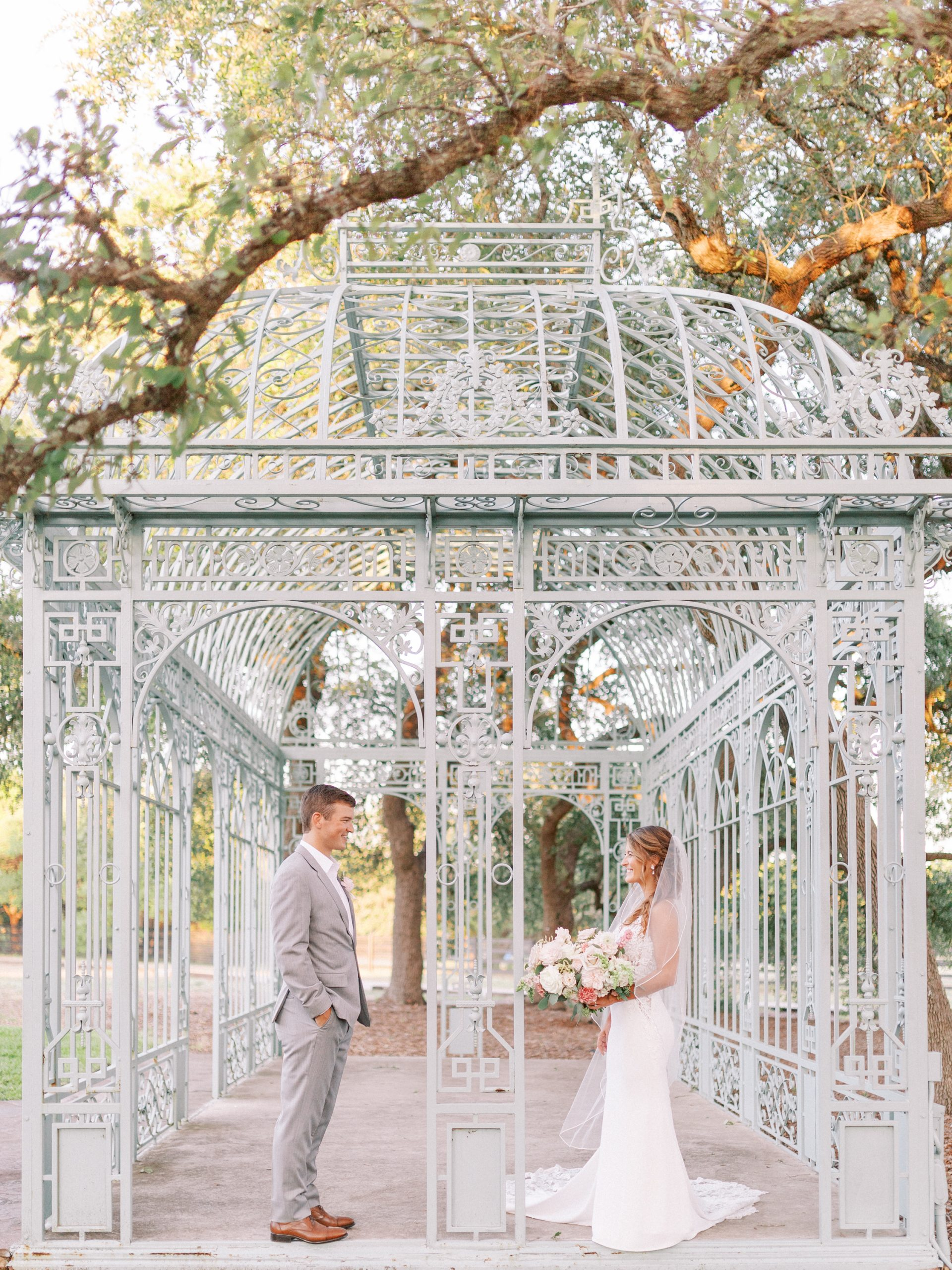 Couple standing under the green cathedral at Ma Maison Austin wedding venue